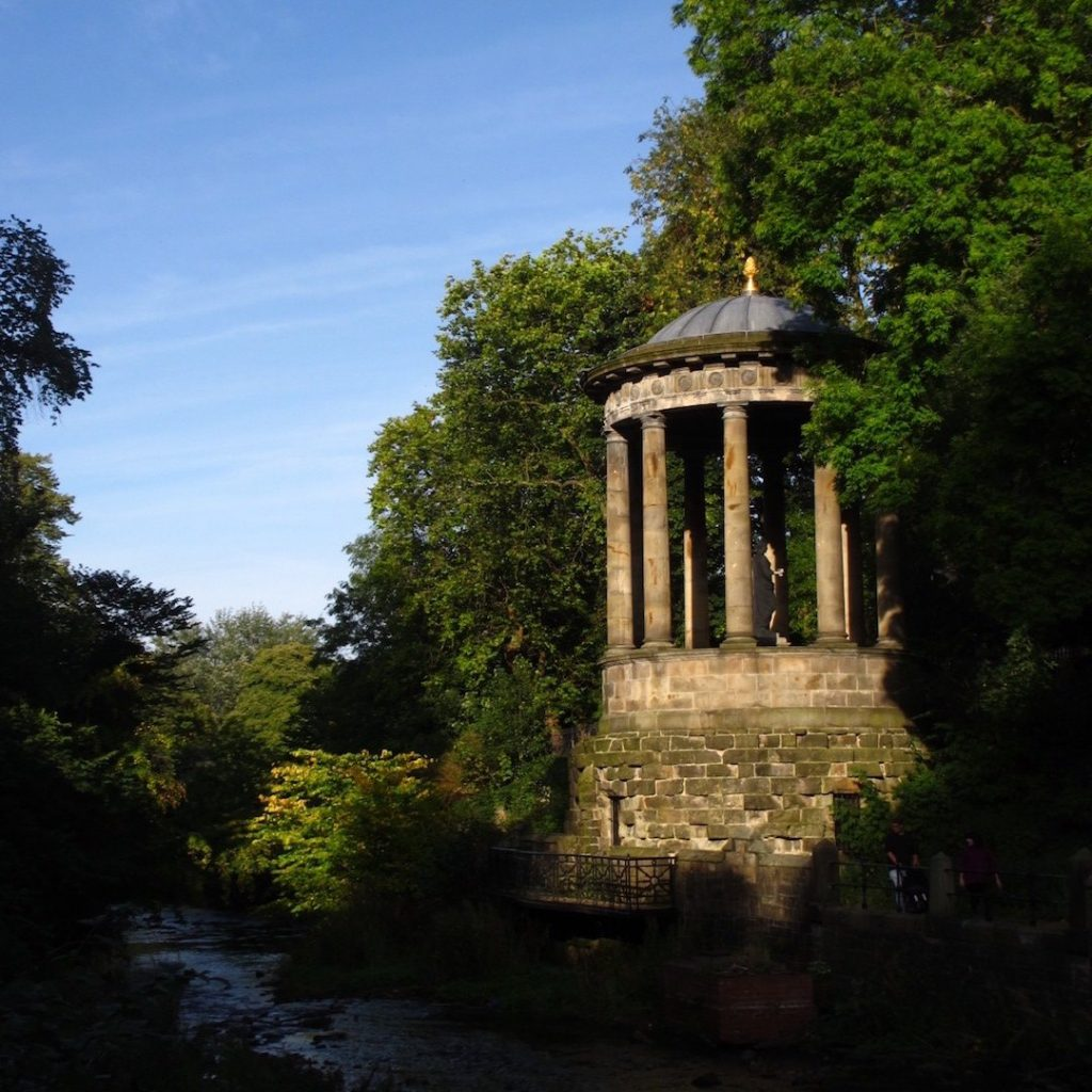 Greek temple architecture of St Bernard's Well next the lush green landscape of Water of Leith, Dean Village