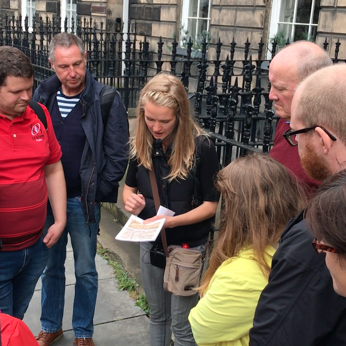 the guide showing maps to the group on Edinburgh New Town Architecture Tour