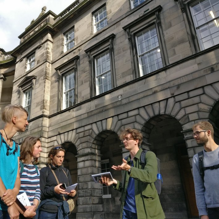 Guide explaining Parliament house on walking tour in Edinburgh