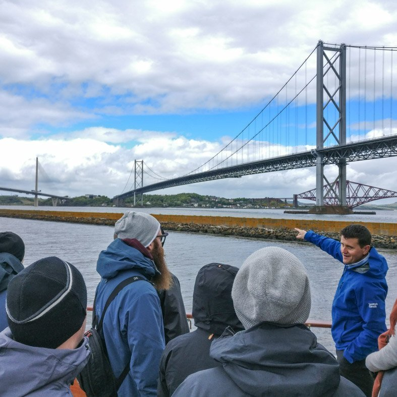 Engineer explaining the Forth Bridges to a group tour near Edinburgh